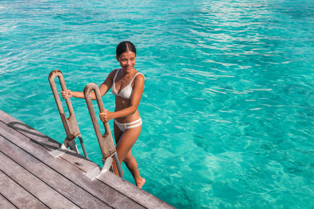 Luxury beach travel vacation woman in Tahiti overwater bungalow hotel villa swimming from ocean deck in French Polynesia island in south pacific, famous getaway destination.