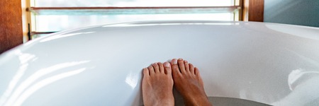 Feet selfie in bathtub woman relaxing enjoying hot water bath in epsom salt foot soak soaking wellness and spa banner panorama, Home lifestyle.