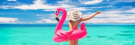 Glücklicher Sommerurlaubsspaßfrauentourist, der Reiseferien auf Strandfahnenhintergrund genießt, bereit für Swimmingpool mit Flamingoschwimmer - lustiges Feiertagskonzept. Standard-Bild