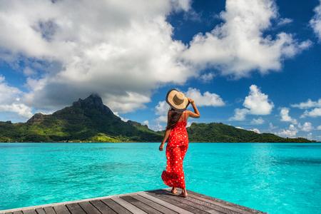 Hôtel de luxe de l'île de Bora Bora femme relaxante à la vue sur le mont Otemanu à Tahiti, destination de voyage de lune de miel en Polynésie française pour les vacances d'été.