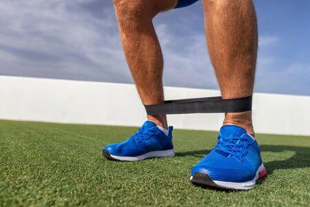 Hombre de entrenamiento de banda de resistencia en el gimnasio entrenamiento de los músculos de la pantorrilla con bandas de goma. Ejercicios de peso corporal al aire libre en el parque. Foto de archivo