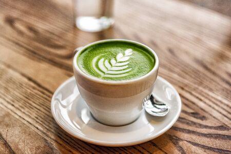 Matcha Latte grüner Milchschaumbecher auf Holztisch im Café. Trendiger Powertee-Trend aus Japan.