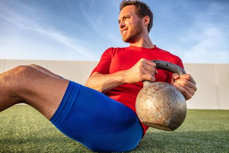 Crossfit training athlete man working out doing russian twists abs situp workout with kettlebell heavy weight in outdoor gym. Фото со стока
