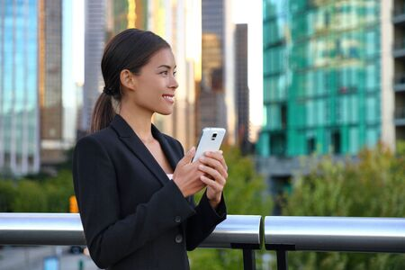 Telefono donna d'affari asiatica in tuta fuori sms su smartphone mobile. Agente immobiliare sorridente felice della donna di affari che lavora facendo uso dello smart phone. Giovane signora caucasica cinese multirazziale al lavoro.