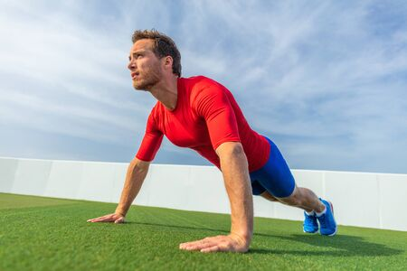 Fit man doing push ups exercise at outdoor gym. Core body workout athlete planking or doing pushup on grass.