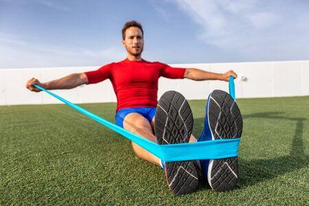 Fitness man training armen met weerstandsbanden op outdoor sportschool of moestuin. Lichaamstraining met apparatuur buiten. Elastische rubberen band accessoire.