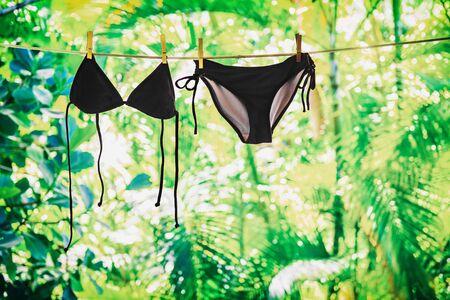 Bikini colgando de la línea de ropa afuera en el balcón. Icono de vacaciones de verano - ropa de mujer moda traje de baño negro lavandería ecológica con fondo verde. Foto de archivo
