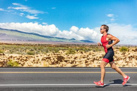 Triathlon runner triathlete man running in tri suit at ironman competition race on road. Sport athlete on marathon run training exercising cardio in professional outfit for triathlon. Fitness Hawaii. Stock Photo