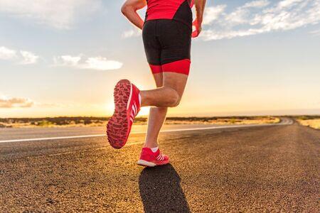 Scarpe da corsa sul corridore triatleta maschio - primo piano dei piedi che corrono sulla strada. Uomo che fa jogging all'esterno dell'allenamento per il triathlon ironman all'esterno al tramonto.