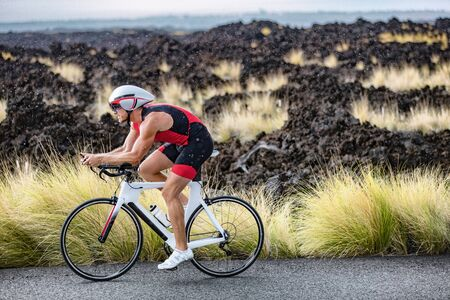 Biking triathlete man cycling road bike under the rain during triathlon race in Hawaii nature landscape. Sport athlete training endurance workout outdoors in Kailua-Kona, Big Island, Hawaii, USA. Stockfoto