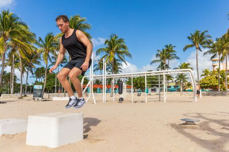 Jump box training man atlhete jumping doing strength workout outside in beach calisthenics park in South Beach, Miami, Florida.