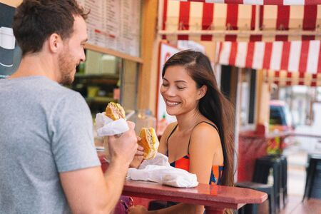 Happy couple eating sandwiches in typical retro cafe in Florida. Cuba sandwich local food. Summer travel tourist lifestyle young Asian woman smiling eating lunch outside. Stock Photo