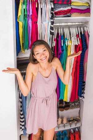 Closet woman confusion needing help choosing outfit or organizing bedroom closet filled with fashion clothing. Funny girl indecision clothes choices, spring cleaning concept. Too much clothes.