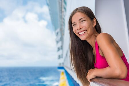 Cruise ship summer vacation. Travel woman tourist happy on luxury cruise getaway smiling at her holidays. Summer european destination holiday. Asian girl enjoying ocean view from ship.