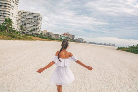 Happy beach woman in white sun dress dancing carefree on summer holidays - vacation lifestyle. Free girl joyful with open arms on honeymoon romantic trip with strapless eyelet white dress. Stock Photo