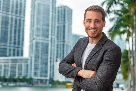 Happy smiling young caucasian businessman man confident with crossed arms portrait wearing smart casual professional blazer on urban city background cityscape. Stock Photo