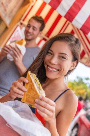 Happy Asian girl eating cuban sandwich at local cafe restaurant in Key West, Florida. Summer travel tourist lifestyle young Asian woman smiling eating lunch outside. Stock Photo