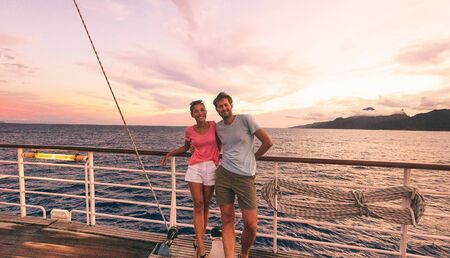 Cruise travel couple on honeymoon vacation cruise ship destination luxury lifestyle. Happy interracial people tourists on boat at sunset sailing away.