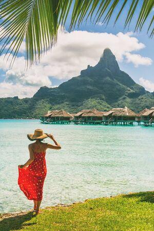 Tahiti resort travel honeymoon destination tourist woman walking on beach of private island at overwater bungalows villas hotels in Bora Bora, French Polynesia. Luxury hotel vacation.