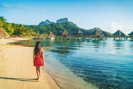Beach vacation woman walking on Bora Bora island in Tahiti, French Polynesia at sunset with Mount Otemanu and overwater bungalows luxury hotel in the background. Stock Photo