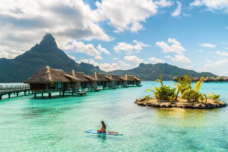 Tahiti luxury resort hotel in Bora Bora ,French Polynesia. Paddleboard leisure activity SUP paddle woman on active vacation in Tahiti, French Polynesia. Mount Otemanu summer holiday. Stock Photo