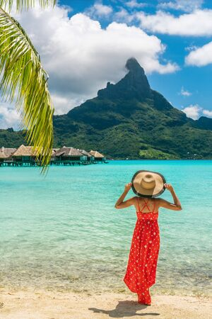 Bora Bora Tahiti exotic tropical vacation destination tourist woman on ocean beach at view of Mt Otemanu in French Polynesia. Girl in red dress and hat relax on honeymoon getaway. Stok Fotoğraf