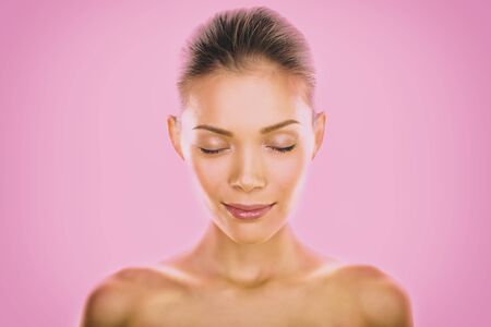 Natural Asian beauty woman model zen with closed eyes meditating calm on pink background. Young girl with slight smile pensive relaxing. Skincare clear dewy skin concept. Stock Photo