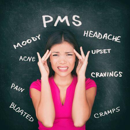 PMS premenstrual syndrome Asian woman holding head in pain having headache, stomach cramps, acne, mood swings with symptoms written on blackboard background in chalk.