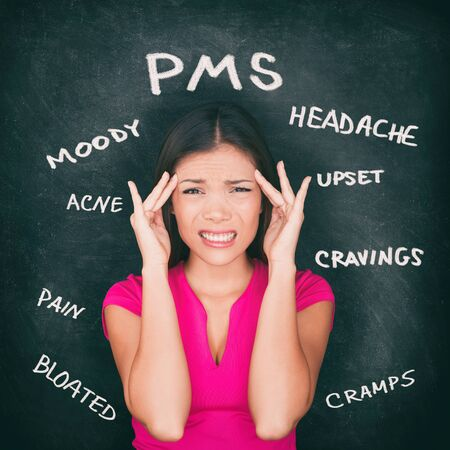 Zespół napięcia przedmiesiączkowego PMS Azjatycka kobieta trzymająca się za głowę w bólu głowy, skurcze żołądka, trądzik, wahania nastroju z objawami wypisanymi kredą na tle tablicy.