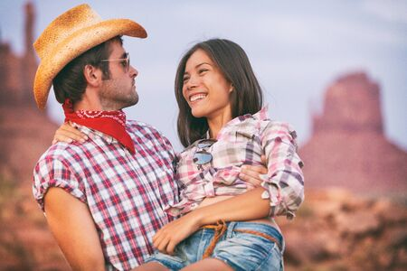 Lovers cowboy and cowgirl in love cute couple in USA backcountry landscape. Boyfriend wearing cowboy hat carrying Asian girlfriend seducing and flirting.