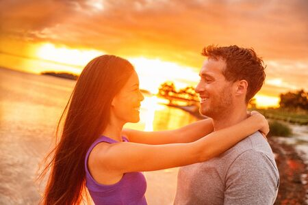 Couple in love laughing at sunset glow on summer beach tropical Caribbean vacation. Happy Asian woman smiling at Caucasian man.