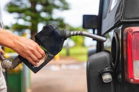 Pomp van het benzinestation. Man vullen benzine brandstof in auto bedrijf mondstuk. Detailopname.