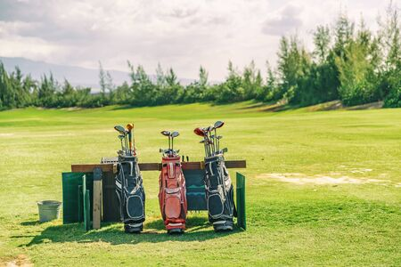 Golfing bags with clubs on golf course green grass background.