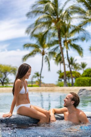 Spa resort couple relaxing enjoying hot tub swimming pool outdoors on summer vacation travel holidays honeymoon getaway.