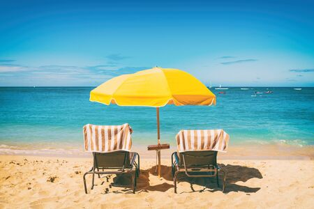 Beach holiday lounging chairs under sun umbrella vacation background. Summer tropical travel destination. Stockfoto