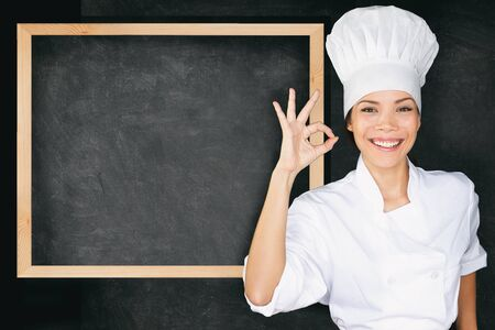 Happy chef doing perfect okay hand sign at empty menu black board background.