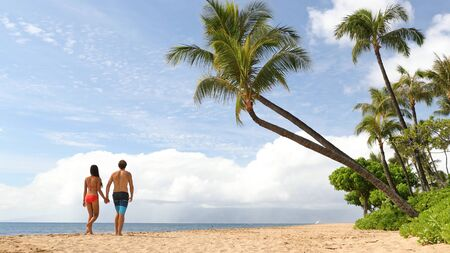 Beach summer vacation couple walking under palm trees in bikini and swim trunks.