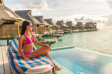 Luxury hotel vacation woman relaxing on private overwater bungalow infinity swimming pool resort room.