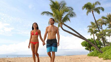 Pareja caminando por la playa. Joven pareja interracial feliz caminando en la playa sonriendo tomados de la mano en trajes de baño. Mujer asiática, hombre caucásico.