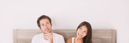 Couple thinking looking up at white copy space panoramic banner. Healthy relationship at home.