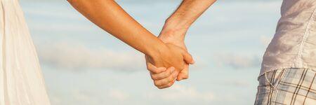Bannerhintergrund des Paares, das Händchen hält, das romantische Sonnenuntergangstrandspaziergang panoramisch verabredet.