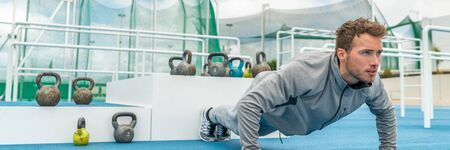 Pushup fitness man exercising in outdoor gym doing workout push up banner panorama. Young healthy male athlete.
