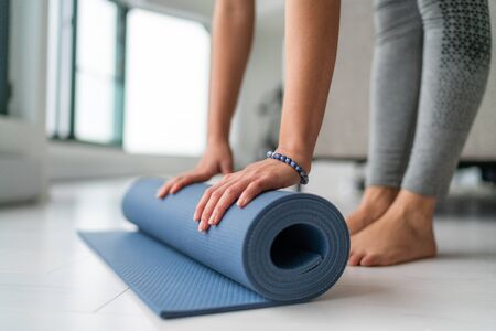 Yoga at home woman rolling exercise mat in living room of house or apartment condo for morning wellness yoga practice. Stok Fotoğraf - 126740950