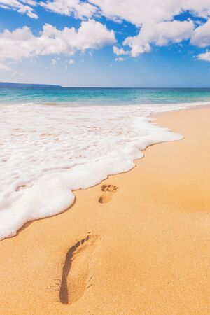 Beach footprint in sand travel vacation vertical background. Holiday footprints disappearing in ocean waves away - footsteps in sand on summer tropical getaway holidays with blue ocean. Reklamní fotografie