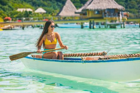 Outrigger Canoe polynesian watersport sport woman paddling in traditional vaa boat. Water leisure activity in Tahiti for recreation competition. Bora Bora overwater bungalow resort hotel. Imagens