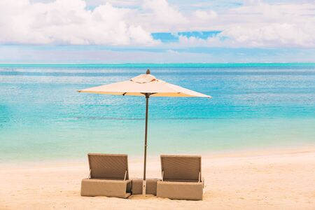Beach luxury resort tropical vacation Caribbean destination. Two loungers chairs with sun umbrella on blue ocean sea water paradise getaway backgroun.d Stock Photo