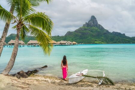 Outrigger Canoe - polynesian woman wearing sarong on Bora Bora beach by traditional vaa boat for paddling in French Polynesia. Bora Bora with Mount Otemanu and overwater bungalow resort hotel.