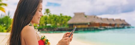 Happy Asian tourist using mobile phone texting sms message on travel holiday vacation panoramic banner of luxury hotel background. Stock Photo