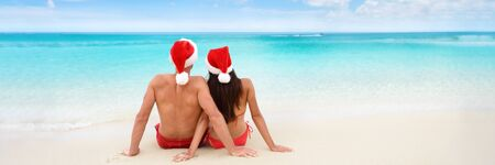 Christmas tropical sun vacation destination vacation holidays santa hat couple relaxing sitting on beach banner background for text advertisement for New Year holiday season. Blue ocean copy space. Stock Photo