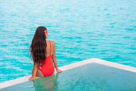 Beautiful woman from behind with long healthy brown hair sitting on the edge of infinity pool over the ocean blue water idyllic travel destination. Relaxation spa lifestyle. Фото со стока - 127186845
